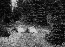 Karen og Gudrun Q. Wiborg med hunden Freya sitter i gresset,