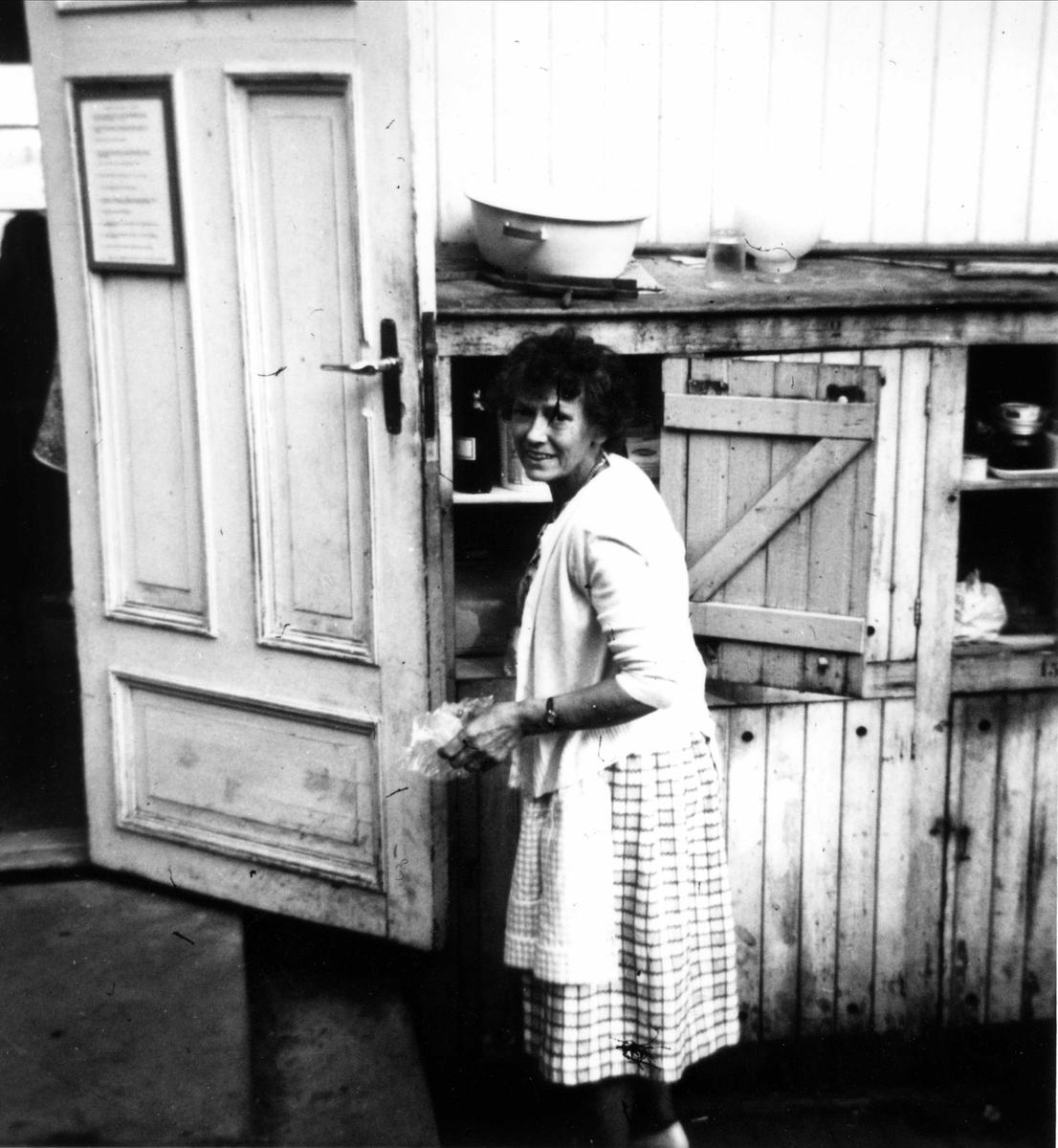 """Kvinne ved uteskap i """"Primusen"""" Oslo Godtemplarungdomslags feriehjem Kirkevik, Nesodden, ca 1964"""
