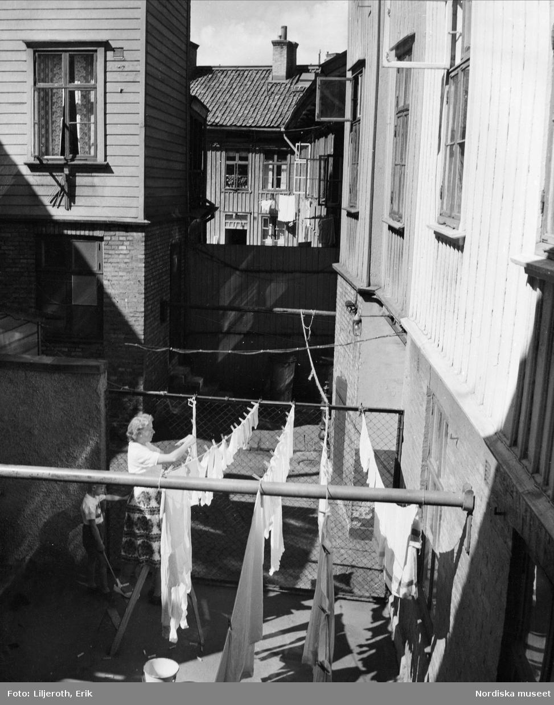 Göteborg. En kvinna hänger upp tvätt på en bakgård