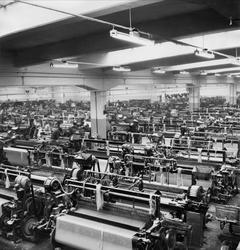 Arbetare och maskiner inne i Karlshams Yllefabrik i Åkershol