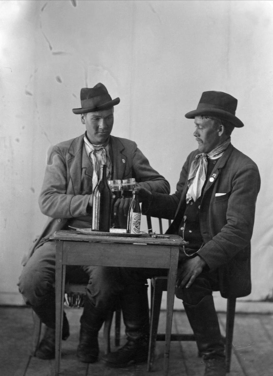 Ateljéporträtt av två unga män vid bord med ölflaskor