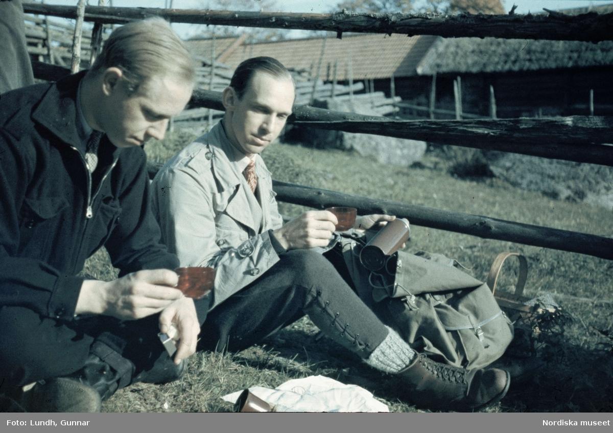Svamputflykt med agronom Nils Suber. Två friluftsklädda män som tar en fikapaus. Ryggsäck och termos och i bakgrunden gärdsgårdar och en husrad.
