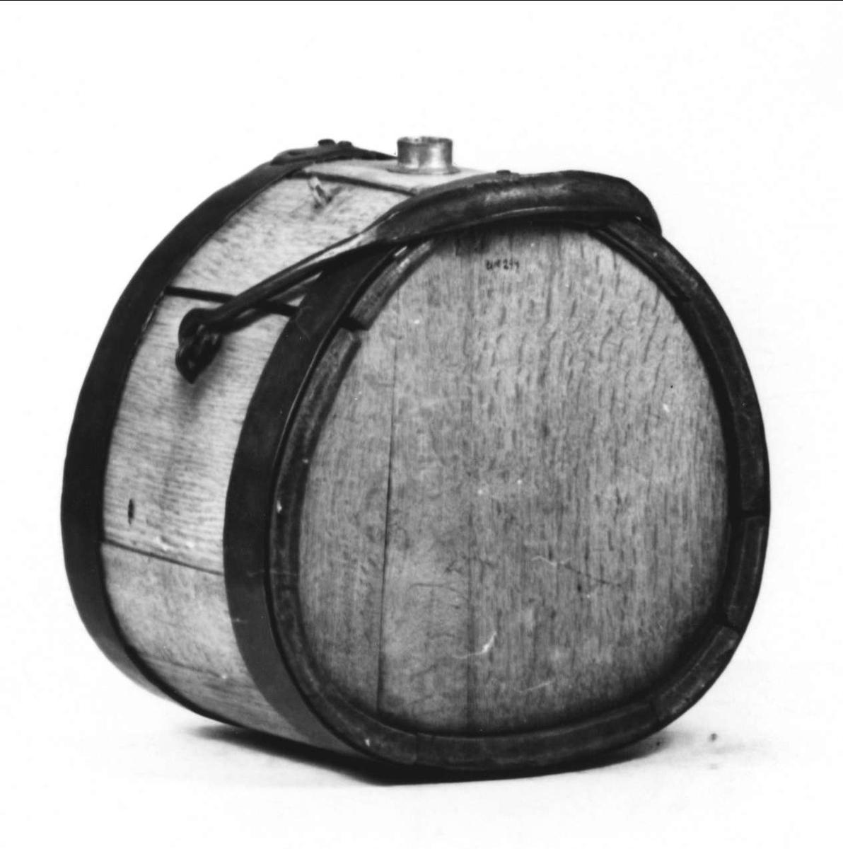 Flaska av trä med band av järn och hank i gott skick. Mynning av tenn. Intill denna liten öppning med träpropp.