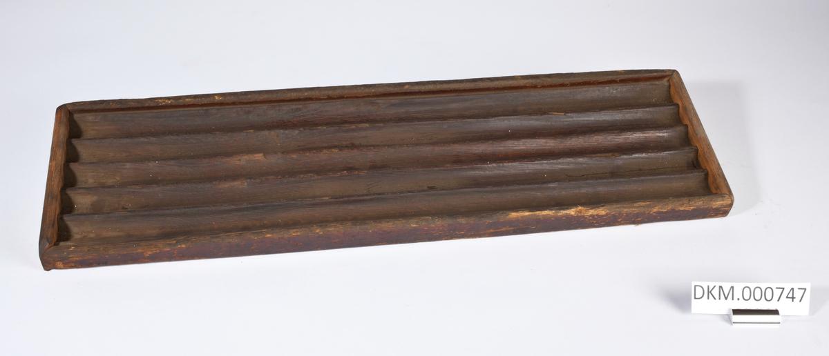 Avlang planke med fem langsgående riller og trelister rundt kantene.