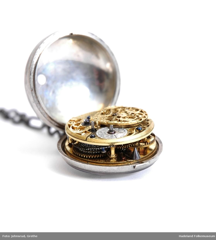Lommeur med klokkekjede. Klokkekjedet er sekundært, i stål. Opprinnelig lås. To kasser i tillegg.  Hvit urskive. Slipt glass. På bakside av ytre klokkekasse er det hamret inn sølvstifter i messingen som danner en rosett. Urverk i messing, rikt dekorert.
