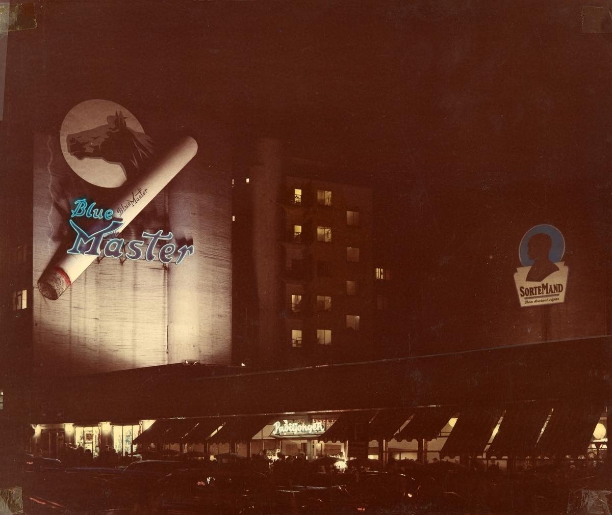 Blue Master og Sorte Mand reklameskilt på fasader over Restaurant Paviljongen ved Hotel Continental i Oslo.