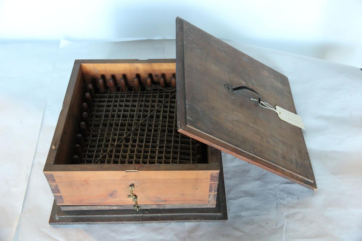 Redningsline kveilet rundt plugger i en treboks som lukkes med kroker for transport.