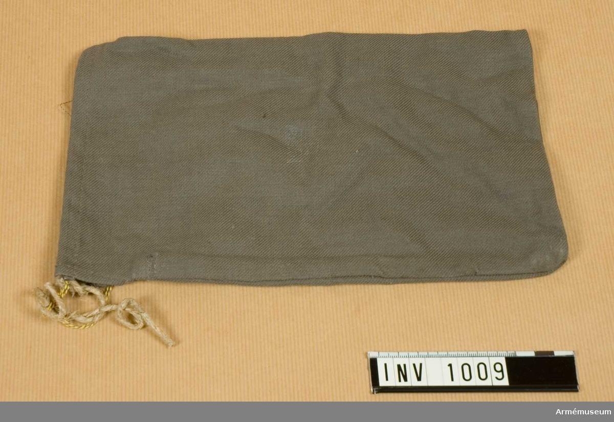 Samhörande nr är 844-849, 862-889, 891-899, 1001-1014.Fodral m/1895, t putstyg.Sydd av gråbrungrönt bomullstyg. Tunnel för dragsko upptill. I detta fall ett papperssnöre. Ett stycke tyg mitt i delar upp påsen i två fack. Påsens ena sida har ett kronmärke. Har tillhört mobiliseringsutrustning vid museet.