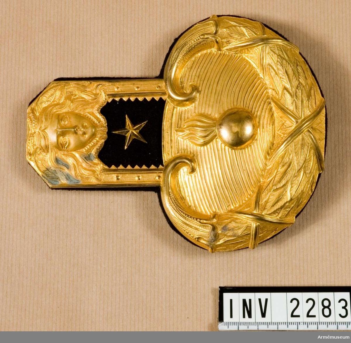 """Av förgylld, ciselerad metall med matta och foder av mörkblått kläde. Go 13 feb 1849 nr 85. Innerst vid kragen ett medusahuvud. Svulsten ytters vid armen är av ett omlindat, kransliknande bladverk som omgärdar bottenplattan varpå en granat vilar. Guldstjärna =  underlöjtnants grad. Foder av kläde och vid epåletthalsen en hake av metall märkt """"MEA, Milit Ekip.akt. bolag."""" Haken skall fästas vid uniformen. Av måtten är axeldelens längd 70 mm och bredd 58 mm."""