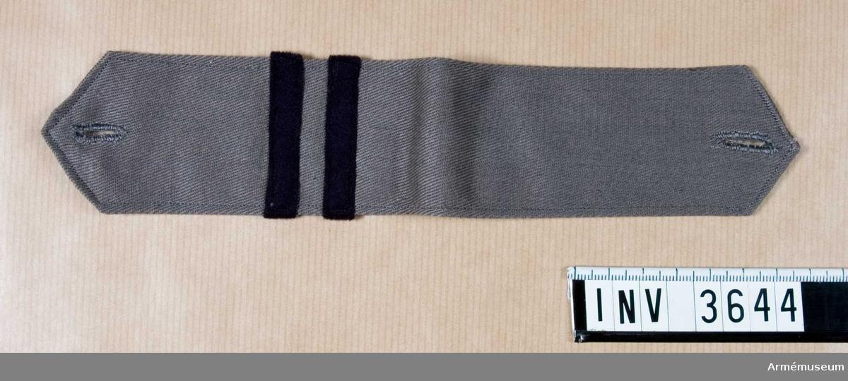 Gott skick. Längd 120 mm (dubbel), bredd 50 mm.Axelklaff m/1942 till blus, SLK. Av grått bomullstyg vävt i  kypert, dubbelvikt med knapphål i vardera ände. Försedd med två tvärgående streck, mörkblå, 10 mm breda. Löjtnants tjänsteställning.