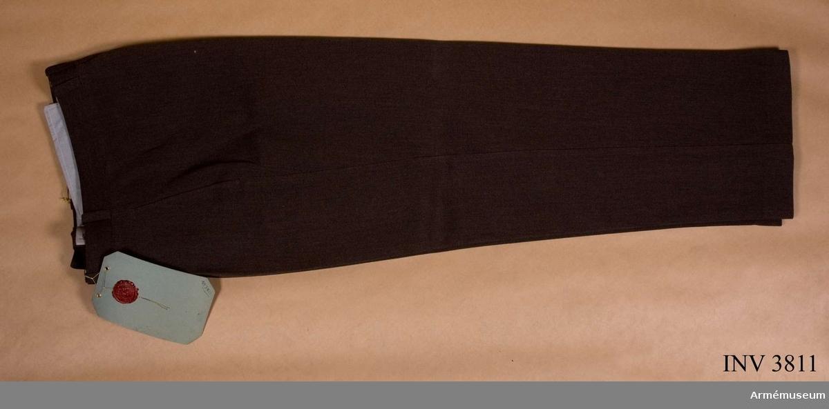 """Av mörkt gråbrungrön kamgarnsdiagonal. Förlängt midjeband m  knapp/knapphål. Två raka sidfickor. En bakficka m slejf,  knapphål/knapp. Utan uppslag. Ett veck på var frambyxa. Sex  hällor f bälte. Foder t midjeband och julp av konstsiden. Till  sid-/bakfickor av domestik, oblandad ull. Vidhängande etikett anger fastställelsedag: """"2.juli 1952"""". Undertecknat av Torsten Nilsson, chef FÖD, C Årman, chef FKE."""