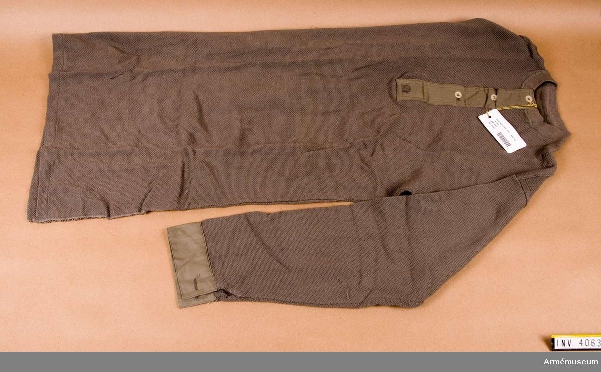 Skjorta m/1939, fält-, mob.det. Trikå. Maskinstickad i våffelteknik. Färg gråbrungrön. Rundringad utan  krage och grön tyglinning i form av knäppslå med tre knapphål  och gulvita nylonknappar. Rakt isydd ärm med manschett nedtill av grönt bomullstyg med gulvit nylonknapp och maskintränsat  knapphål. Skjortan har sidsömmar, nedtill avslutande i ett  sprund, 200 mm högt. Mitt fram på slån är märkt med sluten  krona. Har tillhört rustmästare Olle Skoogs mob utrustning. Fastställd genom Go nr 2300/1946 mom 18.