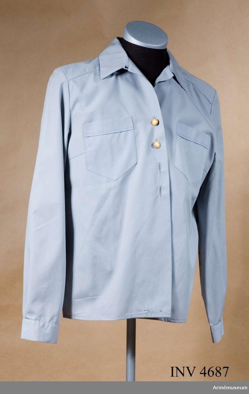 Blus m/1960 kvinnlig. Storlek C 40. Blusen är tillverkad av blågrå skjortpoplin, 35 % polyester och 65 % bomull. Nedvikt krage, framstycket är  försett med besparing. Plagget knäpps med fyra små uniformsknappar m/1939-1960 guldfärg. För knäppning i halsen är  under kragens vänstra sida en polyamidknapp anbringad och på  höger sida invid kragen en knapphålshank. Två bröstfickor med i  överkanten c:a 30 mm breda utåtvikta fållar. Fickornas  nederkanter har spetsformad invikning. Ärmarna är försedda med  c:a 40 mm breda ärmlinningar och en c:a 80 mm lång ärmslits.  Linningarna har knapphål och knäpps med en liten uniformsknapp m/1939-1960 guldfärg. Märkning: På insidans av höger framkant c:a 20 mm från nederkanten finns stämpel Tre kronor AMS 1977.  En vävd storleksetikett C 40 är placerad till höger om stämpeln.Arbetsmarknadsstyrelsen (AMS) hade på grund av den kris som  länge varit rådande inom TEKO-industrin (textil- och  konfektion) satt upp ett antal verkstäder för att ge arbetstillfällen och därför gick många beställningar till AMS.Bilaga 1.