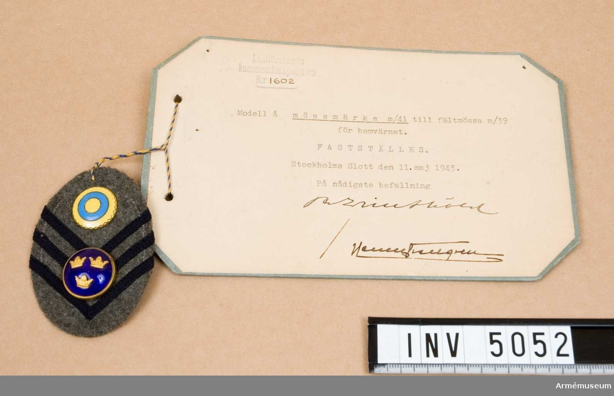 För officer.Modell å ovanstående fastställd 11 maj 1943.Ett elipsformat märke av kommisskläde med i detta fall tre vinklar av mörkblått silkeband. Har knapp för officer m/1865 och neutralitetsmärke i blå och gul emalj.