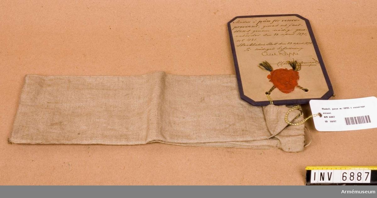 """Av oblekt linneväv med botten/sidor. Upptill dragsko med tvinnad linnesnodd. Vid en söm är ett litet sprund där en liten innerpåse, 100x70 mm, är fästad.  Även den med dragsko/snodd. """"Gillad och fastställd genom nådig generalorder den 23 april  1895 nr 421. Stockholms slott den 23 april 1895 På nådigst befallning Axel Rappe"""" ."""