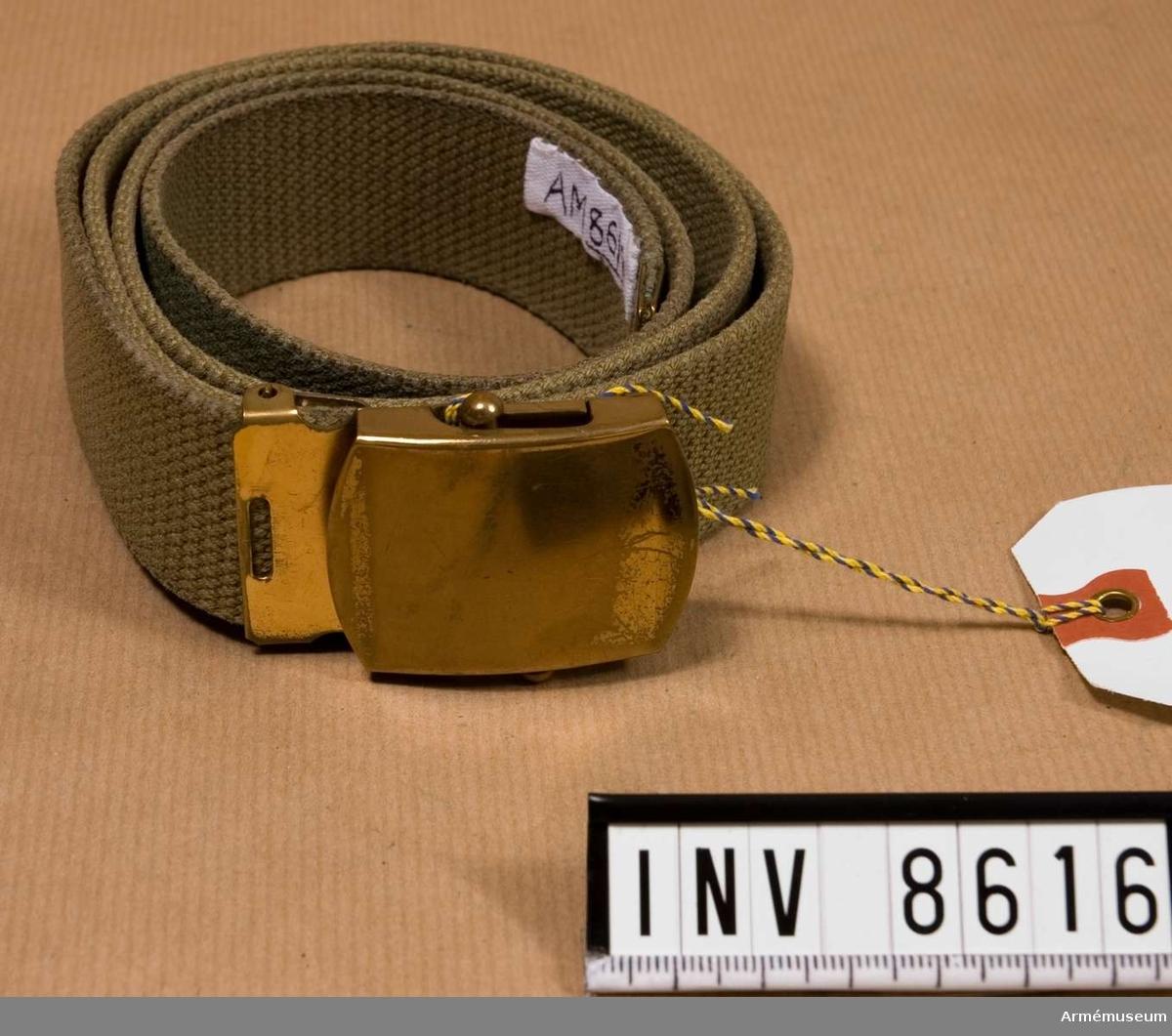 Textil. Byxbälte m/1968, ljusgrönt. Tillverkat av gråbrungrönt textilband med spänne av mässing. Källa Uni A 1977 6:16 d.