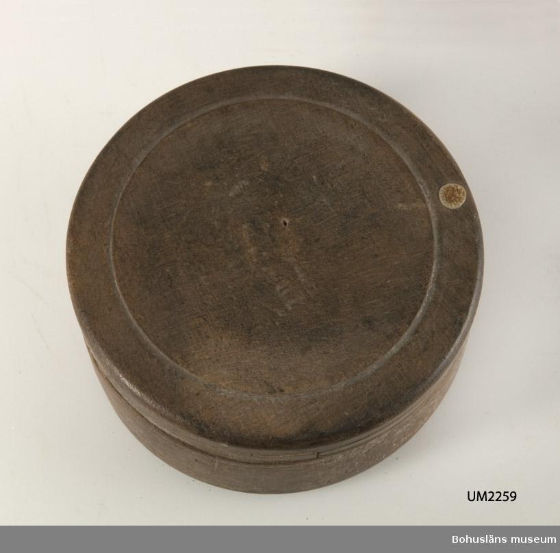 """Cylinderformad, svarvad med lock. Locket har en rund """"spegel"""" på mitten. Linjedekor på lockets och nederdelens kant. Har mörknat på grund av användning. Locket har något defekt kant.  Litt.; Nylén, Anna-Maja, Hemslöjd, Håkan Ohlssons förlag, Lund, 1978, s. 345-349.  Ur handskrivna katalogen 1957-1958: Rund träask, låg m. lock Bottendiameter c:a 10,2 cm. H.: c:a 4,4 cm (inkl. locket) Trä, brunt. Föremålet skevt o ngt defekt.  Lappkatalog: 84"""