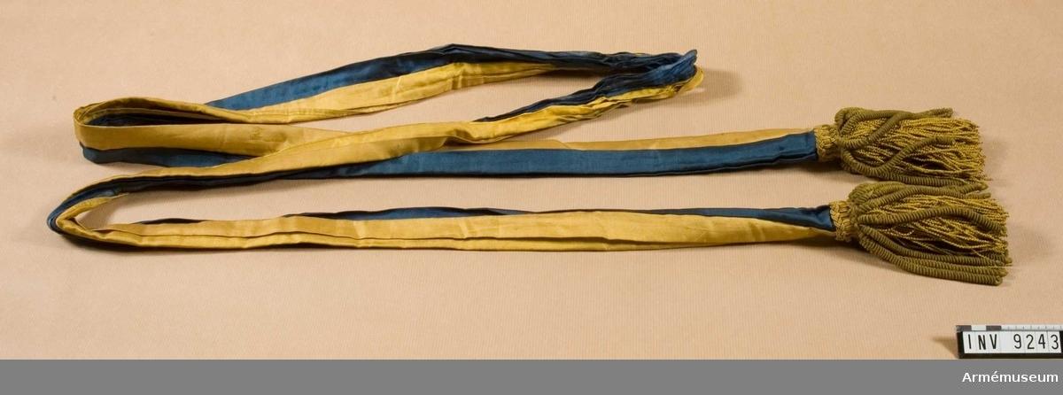 Sydd för hand av hälften blått och hälften gult siden. Kortsidorna är invikta för passning till tofsens hals. Tofsen består av ytterst grova guldbuljoner och innanför dessa en tofs i silkekantiljer, gula.
