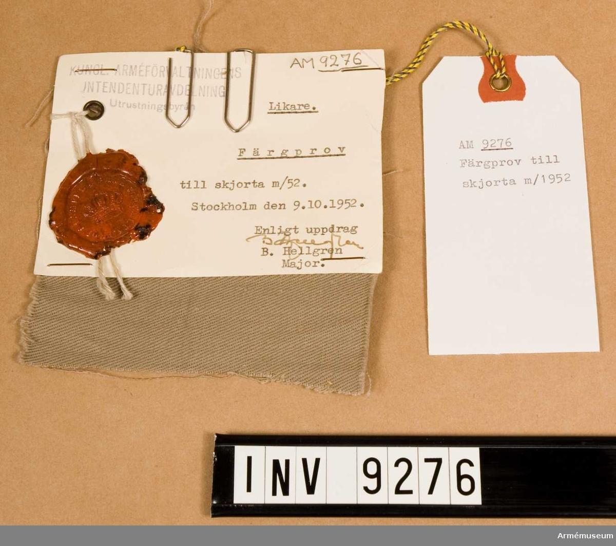"""Ett beigefärgat tygprov. På lapp: """"Likare. Färgprov till skjorta m/52 Stockholm  9.10.1952. Enligt uppdrag (namnteckning) B. Hallgren Major."""". Med stämpel från Kungl. Arméförvaltningens intendenturavdelning utrustningbyrån."""
