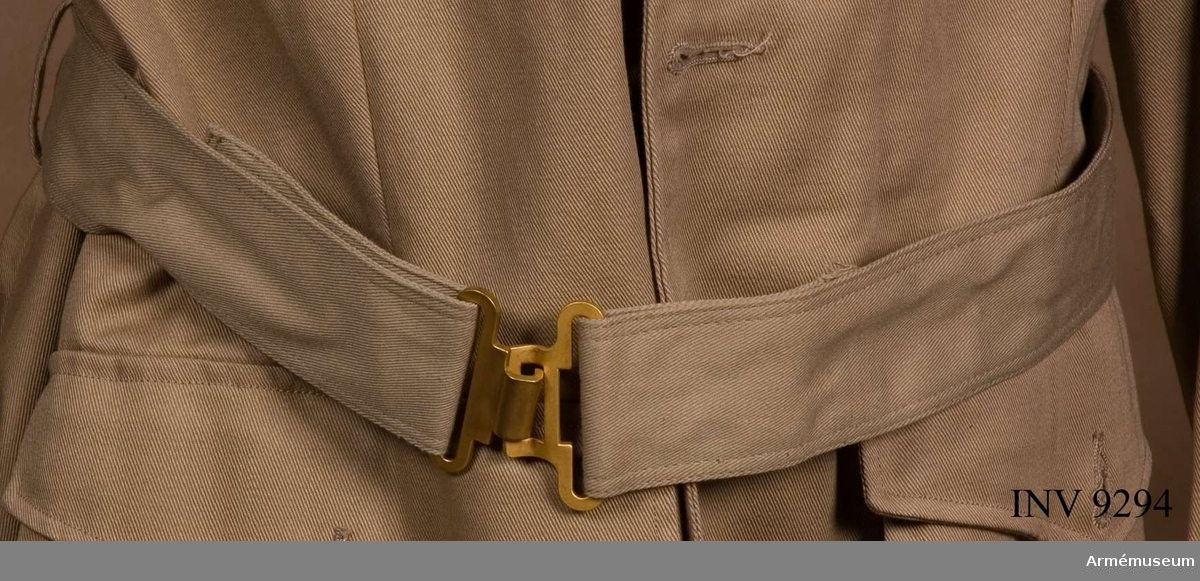 Skärp till vapenrock fm/1961 tropik. Av beigefärgat bomullstyg s k Twills. Sytt dubbelt med dubbla  stickningar i kanterna. Metallspänne i mattförgylld metall i form av hylsa och hake. Skärpet är reglerbart med hjälp av knappar på baksidan. Träs i hällor på vapenrocken.