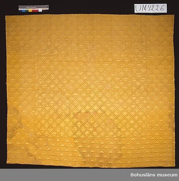 """Föremålet visas i basutställningen Uddevalla genom tiderna, Bohusläns museum, Uddevalla.  Vaddstickat täcke med översida av enfärgat gult siden, mellanlager av ull, foder av kattun (tryckt bomullstyg). Tyget i översida och foder har längsgående skarvar. Översidan består av två bitar, den bredaste 122 cm. Fodret består av tre bitar, den bredaste 85 cm. Fastsydd i kanten på fodersidan är en ca 2 cm bred remsa av kypertvävt rött bomullstyg, småmönstrat med svarta bladslingor. Där remsan är skarvad syns symaskinsstygn vilket innebär att den är påsydd som en lagning tidigast i slutet av 1850-talet.  Täckets yta är uppdelad i mittspegel och ca 30 cm bred bård. Sticksömmen är sydd i diagonalränder som bildar ett rombmönster i mittspegeln. I bården bildar diagonalränder snedställda rutor (9x9 cm), varje ruta är uppdelad i två trianglar, varav den ena (utan stygn) står upp i relief mot den andra halvan sydd med tät sticksöm. Fodertygets hela yta är fylld med mönster i svagt blåtonat rött, mycket mörkt brunt (blekt svart?) och mycket ljust beige (naturfärgad bomull). Mot en långrandig, övervägande mörk, """"botten"""" framstår ljusare tvärränder, utformade som en sammansatt räcka av """"medaljonger"""" med uddig kant. I varannan """"medaljong"""" finns blommor, i varannan mönster med sick-sacklinje och prickar.  Kattuntyget är tryckt på Stora Sickla, på Sickla ö, öster om Södermalm i Stockholm, där Sveriges första kattuntryckeri anlades (med privilegier från 1729). Detta vet man genom att ett mönsterblad med samma mönster finns i den Berchska samlingen på Nordiska museet (Berchska samlingen nr 1195). Anders Berch (1711-1749) bl a professor i juridik i Uppsala, samlade industriprover från 1700-talet, bl a mönster för tygtryckning, med mönster som skulle skäras ut i tryckstockar av trä.  På vissa mönsterblad finns angivet att de har lämnats """"till Hr Debrun"""" dvs Jan de Broen som drev tryckeriet  på Stora Sickla. (Henschen 1992). Att hela ytan är fylld med mönster och att färgerna är tämligen mörk"""