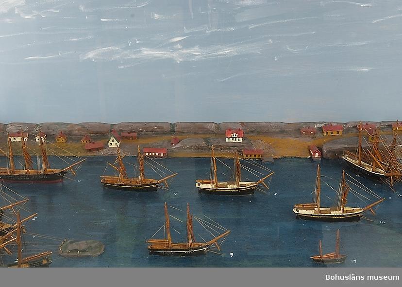 Panorama i monter över Fiskebäckskils hamn på 1880-talet med 33 fartygsmodeller i vinterkvarter. Tillverkad av kapten John Emil Olsson (1880-1950), Fiskebäckskil på Skaftö i Lysekils kommun 1942. Trä, metall, lintråd, gips, glas, målat med oljefärg. Största fartygsmodell längd 16 cm; monter 202 x 61 cm, höjd 53 cm; okänd skala. Vattenlinjemodeller av 30 råseglare, två större jakter och en galeas, uppankrade eller förtöjda. Stående och löpande rigg, däckshus och lastluckor, målade och lackade placerade på en blåmålad platta. Bakgrund av utskurna och målade berg med ett 30-tal hus, sjöbodar och bryggor utspridda längs den djupgående kilen och med gatten ut mot Gullmaren.  Framtill på modellens långsida står textat med vita tryckbokstäver:  FISKEBÄCKSKIL:S HAMN I SLUTET AV 1880-TALET. VID VARJE FARTYGS FÖR STÅR EN SIFFRA SOM HÄNVISAR TILL TAVLAN OVANFÖR MONTERN. Den maskinskrivna texten berättar: Fiskebäckskils hamn i slutet av 1880-talet.  I vinterkvarter upplagda i Fiskebäckskil hemmahörande segelfartyg. 1. Skonert Gustaf, befälhavare M. Johansson 2. Brigg Clinton, befälhavare J. Bengtsson 3. Skonertskepp Nordstjernan, befälhavare Am. Olsson 4. Barkskepp Diana, befälhavare H. Andersson, Gåsö 5. Skonert Elise, befälhavare Joh. Gren 6. Barkskepp Celeritas, befälhavare C. Bengtsson 7. Brigg Ben:s Mollén, befälhavare Joh. Månsson 8. Skonerter Elida, Magnus Gren 9. Skonert Olga, befälhavare C. Jansson 10. Skonert Idun, befälhavare Ferd. Gren 11. Skonert Ida Sofia, befälhavare O. Simonsson 12. Skonert Gustaf, befälhavare J. Andersson 13. Skonert Alfa, befälhavare A. Kihlman 14. Skonert Klara, befälhavare P. Berntsson 15. Jakt Tärnan, befälhavare P. Persson 16. Barkskepp Bohuslän, befälhavare H. Jonasson 17. Galeas Blenda, befälhavare B. Wahlberg 18. Jakt Wiktor, befälhavare J. Hansson 19. Brigg Gerda, befälhavare F. Edman, Flatön 20. Skonert Norma, befälhavare A. Larsson 21. Brigg Gustava, befälhavare J. Larsson 22. Skonertskepp Uddevalla, befälhavare J. Mattsson 23. Skone