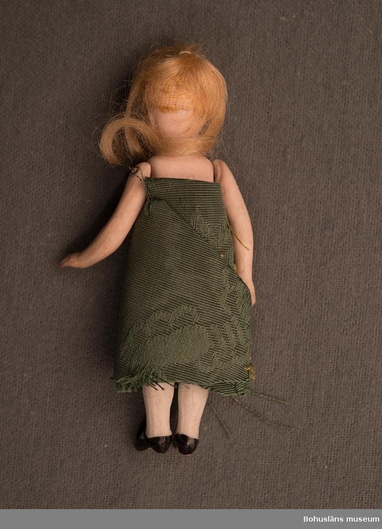 Docka i porslin med lösa armar och ben. Sammanfogade med ståltråd som går genom kroppen. Dockan har blont hår, blå ögon med effektstreckar runt ögonen. Bruna ögonbryn. Benkläder av spetstyg och en klänning av grön satin. På ryggen är stansat ID.