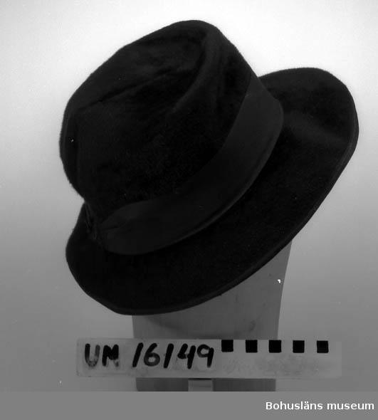"""398 Tel.2211.  Hatt av velour i s.k. herrmodell.Ca 10 cm hög kulle,ca 7 cm brett  brätte som är smalare i nacken (ca4,5cm). Brättet kantat med smal ripsband med infälld ståltråd.4 cm brett svart ripsband runt kullen. Rosett i nacken saknas.  """"Svettrem"""" av svart ripsband med tillverkarens märke. Tämligen välbevarad."""