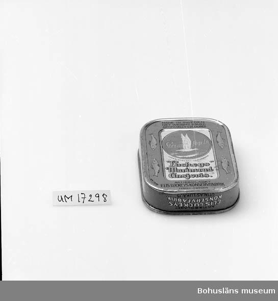 """Blå burk, guld-, svart och vit dekor. Blankt lock.  Text på sidan: """"Skinn & benfri marinerad ansjovis i dillsås. Aktiebolaget Elis Luckeys Konservfabrik uttalas lukäjs.""""  Engelsk parallelltext. Samma text i botten samt """"stormfågeln inregistrerad varumärke"""" och engelsk deklaration. Öppnas med nyckel. Se UM17232."""