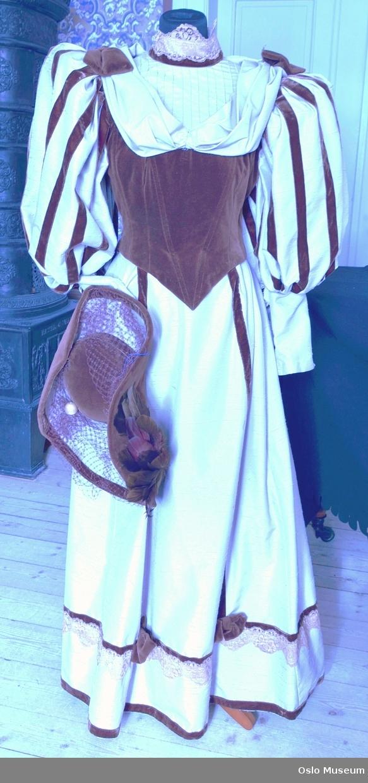 Lang kjole i beige, silkeaktig stoff. Kjoleliv og detaljer i brun fløyel. Blonder på krave og skjørtdel. Hatt i samme stoffkombinasjon med fjær og hattenål.