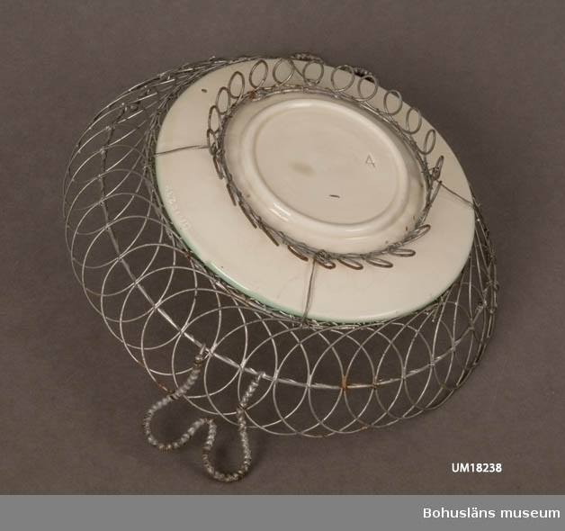 Assiett av keramik (majolika) med kantgaller i järntråd, något rostat. Jämför UM18237.