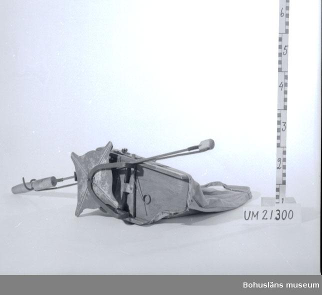 594 Landskap BOHUSLÄN  Påse, fröbehållare, att bära runt halsen. Påsen har träbotten med en lucka. Under botten är det en roterande fröspridare gjord av metall. Luckan och fröspridaren regleras med ett stråkeliknande handtag. Ett hål samt lagningar på påsen.  Omkatalogiserat 1996-11-26 GH.  UMFF 8:12
