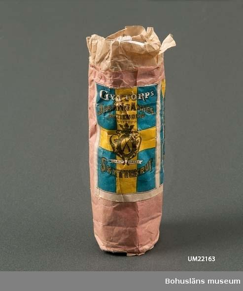 """Ljusröd förpackning utan krut med text på svenska flaggan: """"Gyttorps sprängämnesaktiebolag, Gyttorp. Skyttekrut. Varumärke."""""""