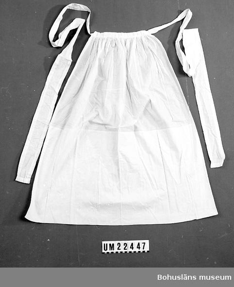 594 Landskap BOHUSLÄN  Förkläde av vitt bomullstyg med långa midjeband. Hopsytt av två bitar.  UMFF 109:7