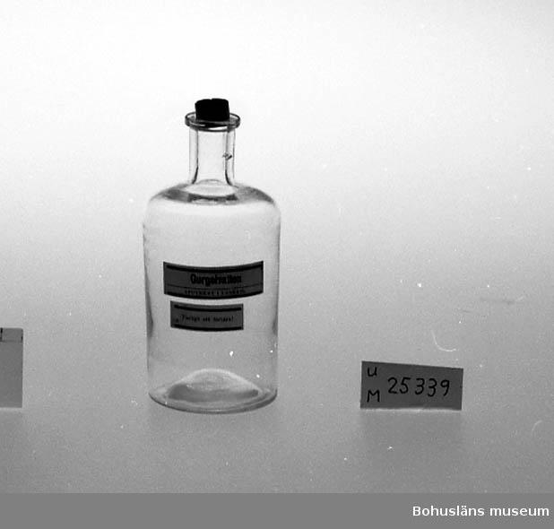 """471 Tillverkningstid CA 1900 594 Landskap BOHUSLÄN  Etikett med text: """"Gurgelvatten APOTEKET I LYSEKIL Farligt att förtära!"""". Innehållet har tömts av Bohusläns museum."""