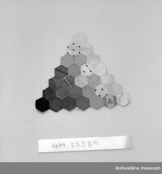 """594 Landskap BOHUSLÄN 394 Landskap BOHUSLÄN  Sexkantiga bitar av dels siden dels sammet sammansatta i lapptäcksteknik. Har varit del av handväska. Delarna 2,5 cm i diam. och sydda över pappskivor innan de sammanfogats. Sydd av Jessy Thorburn  f. Macfie f. 1 sept. 1790 i Skottland, d. 14 aug. 1863 på Kasen, Uddevalla och gift med godsägaren, handlanden m m William Thorburn  f. 12 sept. 1780 i Skottland d. 9 febr. 1851, Kasen, Uddevalla. De invandrade som de första av släkten T. 1827 till Kasen. Se """"Släktföreningen Thorburn - Macfies tidskrift"""". Detta stycke av handväska ärvde bl. a. sedermera systrarna Rosa och Margret   Thorburn, Villa Skanskullen, Uddevalla, sondöttrar till ovanstående. Av dem fick Ruth Thorburn stycket till sin samling modell- och mönsterförlagor hon använde i sitt arbete. Ruth och Dagmar Thorburn systrar och sondöttrar till Wiliam och Jessy Thorburn.  Personuppgifter om Ruth T. se UM025385."""