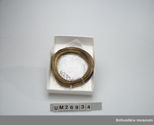 Många meter tunn mässingstråd uppvirad i cirkelform. Några utstickande ändar. Bitvis färgad med vitaktigt brunlila (troligen utspilld) färg.