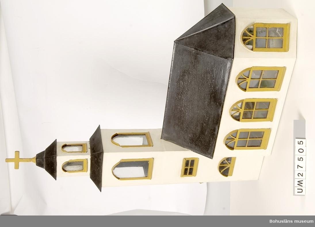 """Modellen föreställer Lysekils gamla träkyrka, uppförd på 1790-talet. Modellen är tillverkad i plåt,  har fönsterglas och står på en träsockel med tillhörande lös trappa.  Fasaden är vitmålad och skall se rappad ut, taket svart, fönster- och dörromfattningar är gulmålade. Kyrkan står på en gråmålad träsockel med reliefskuren """"stenmur"""". Tornet avslutas med ett kors. En liten, lös trappa leder upp till ingången. Långhusets fasad har tre fönster på södra sidan, två fönster och en ingång på norra sidan med nyckel till dörren, två fönster i koret, en ingång i torndelens västra del samt två lunettfönster i tornets första våning.   Interiören består av ett vitmålat altare, en altartavla bestående av en inramad reproduktion föreställande Jesu ansikte. På altaret står två ljusstakar i pressglas, fästade med metallband. En gulmålad, dekorerad altarring och en nummertavla med psalmer fullbordar korets inredning. I en grönmålad predikstol står prästen, en målad docka av biskvi, inköpt för 5.25. Nedanför predikstolen stå två gulmålade  bänkar,  bakom ingångsdörren står ytterligare tre bänkar, utmed södersidans långvägg står sju motsvarande bänkar. Tak och väggar är gråmålade, golvet är grönmålat. I tornet hänger en klocka med kläpp."""