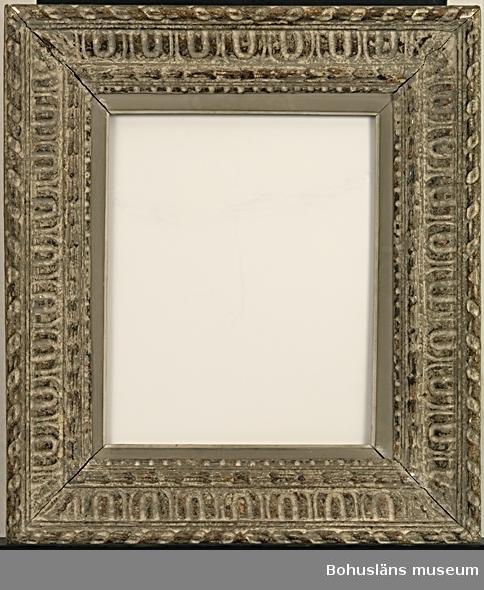 """""""Impressionistram"""" (se nedan). Rikt ornamenterad kraftig fururam med patinerad yta i grå, bruna och brunsvarta nyanser. Det gråvita skiktet är medvetet förslitet med ett verktyg. De översta, matta skikten består av ett mörkare grått färgskikt ovanpå en ljusare, som omväxlande framträder tillsammans med  det underliggande skiktets bruna, svartnade och blanka yta.  De skurna dekorelementen sett utifrån är flätband, dubbel hålkäls-, äggstavs- och x-list, samt enkel hålkäls- och hopplist. Gråmålad, neutral inkantlist avslutad med vitmålad hålkälslist närmast bildyta, B 2,1 cm. Listen är en senare komplettering. Spikmärken på öppningens insida visar att den har använts. Dagöppningen är 40,0 x 32,3 cm.   Uppgifter i samtal med rammakare Ralf D. Weber, Sjuntorp: Rikt dekorerade ramar utgörs annars oftast av en stomme av trä med dekor gjord av pastellage/tryckmassa. Massan är ett plastiskt material som består av många olika ämnen; bl a krita och animaliskt lim, gips, glycerin och kokt linolja, vilken pressas i gipsform. Det ännu  fuktiga materialet tas försiktigt ur formen. Innan påfästning värms det färdiga dekorelementet i vattenbad så att rammakaren kan göra finjustering på plats. Materialet tål att dras något och kan på så sätt korrigeras. Dekorelement kan också kavlas ut mellan mönsterskurna valsar. Dessa limmas sedan fast mot ramen. Ramen får sedan ligga i rumstemperatur och torka under en vecka. Ofta kan man se lagningar och kompletteringar i hörnen. För att dölja mötet mellan dekorbanden i ramens hörn har tillverkaren ofta placerat en extra dekoration ovanpå hörnets skarv. Impressionistramar, eller """"franska ramar"""" som de kallades vid tiden kring sekelskiftet 1900, blev omtyckta till målningar gjorda av de franska impressionisterna på 1880-talet. Cezanne, Degas, m.fl. """"återupptäckte"""" de ornamenterade ramtyperna. Det blev det populärt att nytillverka liknande ramar. Man använde i flera fall de gamla valsarna för tryckmassan vilka ofta fanns bevarade hos rammakaren och"""