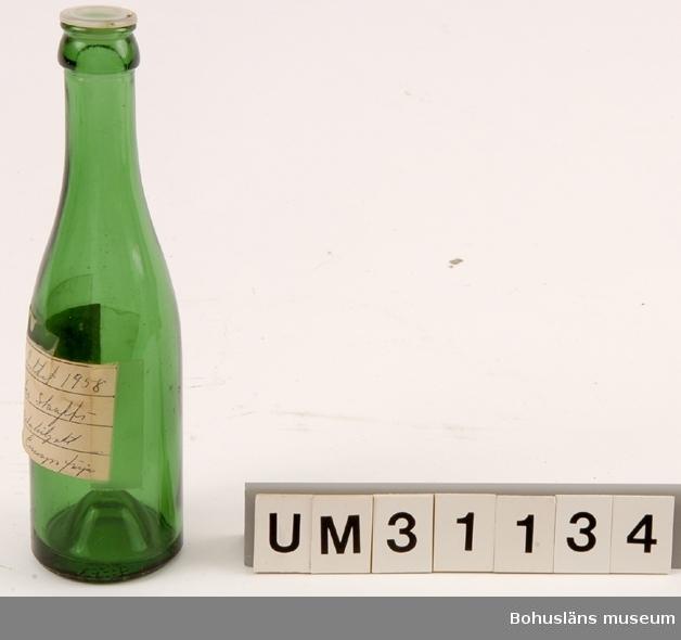 Bryggeriflaska, ca 20 cl., i grönt glas med plastkork. Påklistrad papperslapp där Bernhardson skrivit: Flaskpost hittat 1958 vid... ... ...  Funnen som vrakgods i Bohuslän (?)  Bernhardson beskriver barnens vrakletning i boken  Bohuslän - från Wämmer ock Kräppe  s. 128: Ätter e hale västa å massa lanfall brogga ongane sprenge langs strännena å röra i tanga - de leda ätter granne bôttlar mä konsti korkar å färger, de sanka på sånna. (Efter hård västanvind och högvatten brukade barnen springa längs stränderna och sparka i tången. Barnen sökte efter vackra buteljer med olikartade skruvkorkar och färger. Man samlade på sådana flaskor). Tidsbild 1920-talet  Litt: Bernhardson, C. G.: Bohuslän - från Wämmer ocH Kräppe. Uddevalla 1985.  För ytterligare upplysningar om förvärvet, se UM31100.
