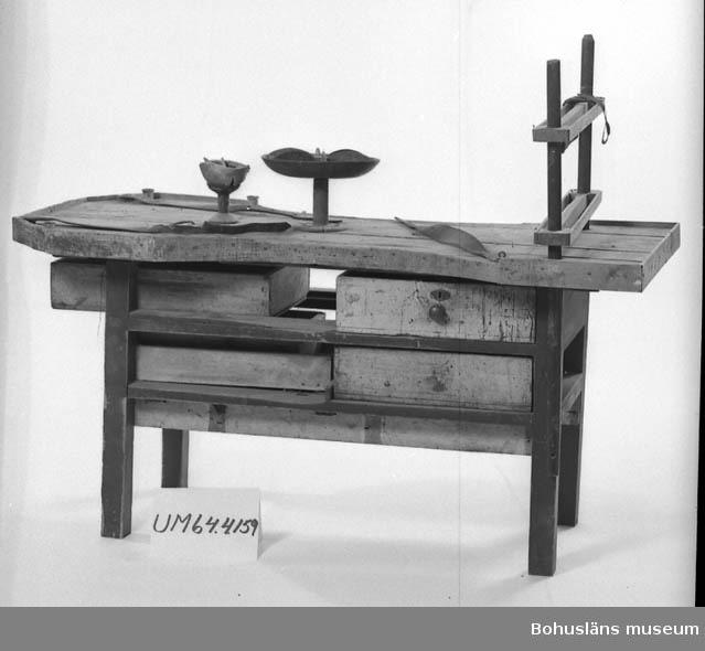 """471 Tillverkningstid 1910-1930? 503 Kön MAN  Arbetsbord med 2 arbetsplatser, egentillverkat. Skivan är ihopspikade brädor, med sarg runt om, utom vid insågningarna på arbetsplatserna. Sargen är 1 1/2 cm hög på insidan. Benställningen, sekundär användning, är brunmålad. Även lådorna även  användning. De på långsidorna är genomgående och kan dras ut från båda sidor. Den övre lådan består av två mindre lådor ihopsatta till en. Lådorna har knopphandtag, en av dem är försedd med lås, gråmålade. Två lådor på ena kortsidan, den övre är 30 cm bred. Lådan innehåller lösa skinnbitar av varierande storlek, färg och form. Gråmålad utsida och knopphandtag. Den undre 25 cm bred, brun och handtaget är en ring.  På bordet finns fastspikat en liten """"skål"""", på fot, höjd 12,5 cm , diam 10 cm. Skålen i läder, fästet i metall och foten i trä. Den innehåller lite pligg och lösa träbitar. På bordsskivan finns även tre läderremmar, två på ena kortändan i varsitt hörn och en i ett av de motsatta hörnen. Det har troligen suttit en fjärde rem i det fjärde hörnet, det finns märken i bordet. Remmarna är ca 55 cm långa, avsmalnande med ca 10 hål i varje, en är trasig. Längs insidan på sargen tre små plåtburkar med vax. Mot en kortsida står en träställning, 52 cm lång. Den består av två rundstavar som går igenom bordskivan och är fästa i bordbenen. Mellan dessa stavar sitter två slåar, 7 cm breda med 17 cm mellanrum. Slåarna är fasade längs med och en yttre kant, av ofärgat trä. Rundstavarna är svartmålade. På den ena hänger en dubbelvikt brun skinnbit och en packningsring. På ena slån sitter en orange 8:a i plast limmad.  På bordsskivan sitter också ett par skruvöglor, fyra tunna metallbrickor, sammansatta två och två med ståltråd. Mitt på bordet spår efter och skruv till pliggfat UM64.04.080. Längs utsidan på sargen sitter till vänster om en arbetsplats en läderrem fastspikad, som upphängningsanordning för verktyg. Bänken är väl använd, sliten och nött med mycket fläckar av olika storlek och ku"""