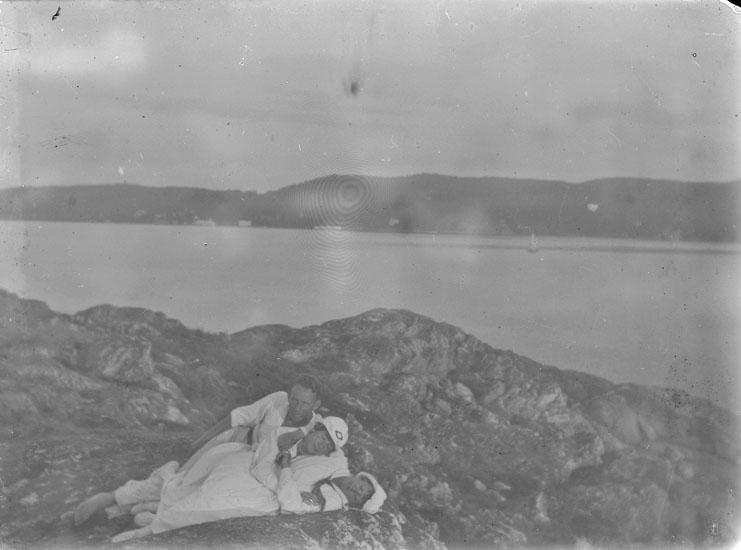 """Enl. text i blå bok: """"En man och två kvinnor liggande på berg i skärgården."""""""