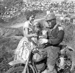 Miss SM delar ut blommor till en förare på SM Motocross, Kur