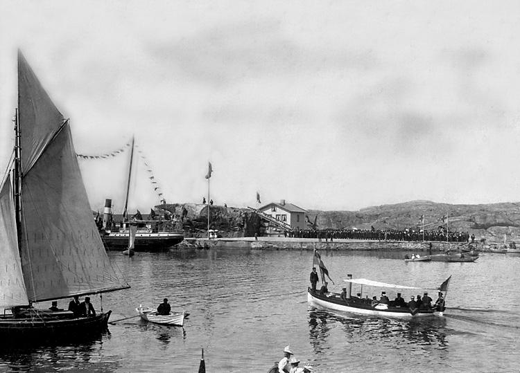 Medlemmar ur Coldino-orden placerar ett kors på kullen Malepert.  Ett antal båtar syns i vattnet runt omkring. En större folksamlings står på kajen.