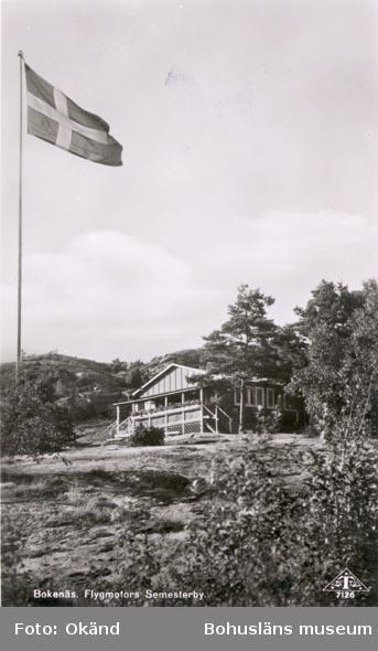 """Tryckt text på kortet: """"Bokenäs. Flygmotors Semesterby"""". Noterat på kortet:""""ERIKSBERG BOKENÄS SN. SKAFTÖ (BOKENÄSET)"""". """"Kortet köpt 9 AUG 1955""""."""