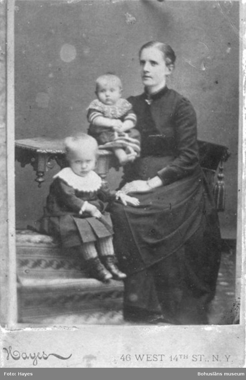 """Text på kortets baksida: """"Johan Edvard Johansson fru Amanda Johansson med sina två söner, på bordet Edvard """"Eddie""""."""