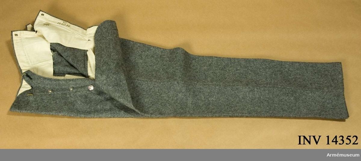 """Grupp C I. Da. bukser, av grått kläde, långa, med två fickor på sidan och på baksidan spänntamp av kläde med spännen. Järnknapparna är: tre st på sprundet och sex st för hängslen. Foder av vitt tyd med stämpel """"19 MD 39"""", MD = Munderingsdepot, """"7 R"""". Enl papperslapp från Töjhusmuseet tillhör denna rock: """"Ingeniör, Menig Uniform m/1915, Bukser"""". Enl Handbuch der Uniformkunde, Prof. R. Knötel-Sieg, Hamburg 1937, sid 142: Under världskriges lopp (1914-1917) infördes i danska armen uniform av stengrått kläde.Enl Granberg."""