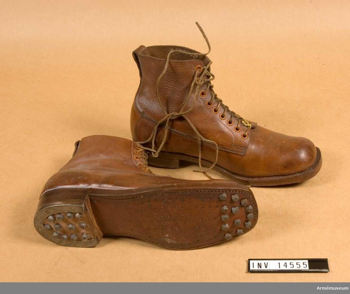 Grupp C I. Snörskor av grovt brunfärgat läder med inskärning på framsidan och försedda med 6 par järnringar för att snöra skorna med snören av läder.