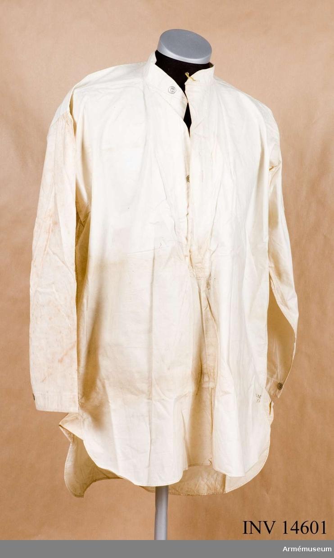 """Skjorta av vitt bomullstyg med fast upprättstående krage med långa ärmar. Kragen och bröstöppningen knäppes med två metallknappar. På varje ärmuppslags sprund en knapp av samma sort. PÅ skjortans framsida stämpel: """"W"""" upprättstående pil """"D"""", """"13"""" under pilen."""