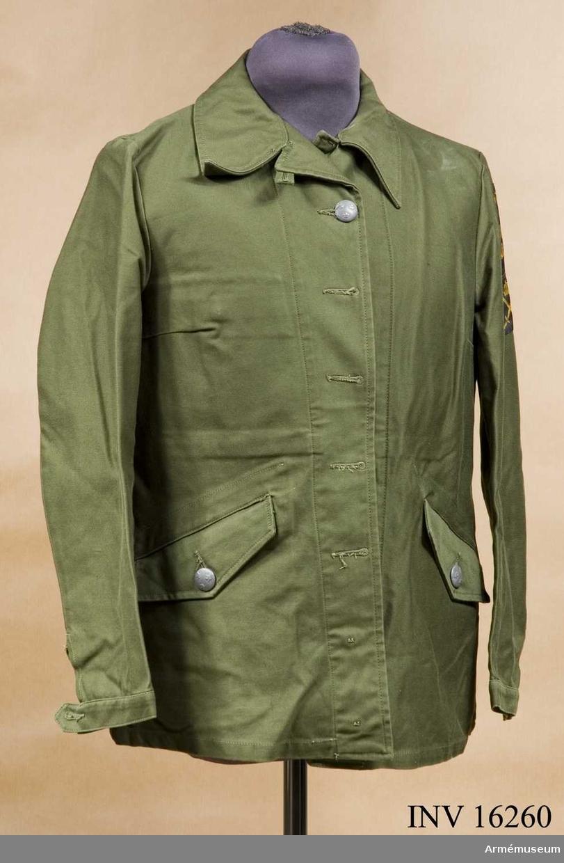 Tillverkad av olivgrönt tyg, är enradig och knäpps med fem stora knappar m/1939, är högknäppt i halsen, har två snedställda sidfickor samt reglerbar ärmlinning. På vänster ärm nationalitetsmärket och under det armétecknet vävt i gult.